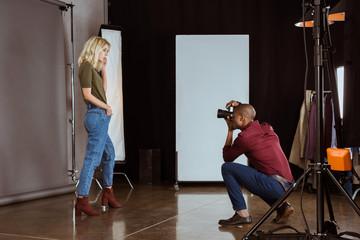 african american photographer taking photo of attractive model in studio