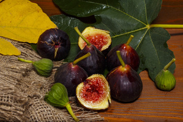Ripe sweet figs with green leaves. Healthy Mediterranean fig figs. On a wooden board with burlap.