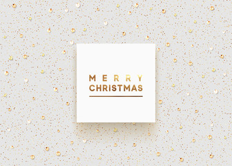 Christmas background is strewn with precious stones and bright sparkles. Merry Christmas lettering in square white frame, luxury text of gold color.