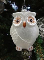 Елка украшена красивым новогодним стеклянным украшением –белая сова, покрытая блестками