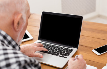 Senior man using laptop with blank screen mockup