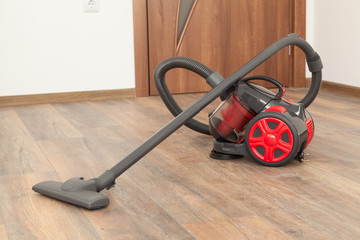 Vacuum cleaner on the wooden floor. Cleaning home