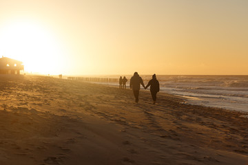 Two holding hands walking towards the sunset on a beach