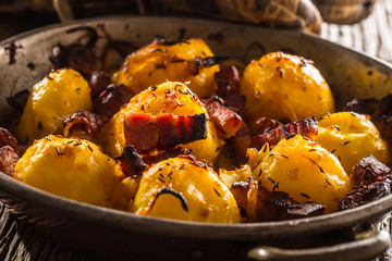 Potatoes. Roasted potatoes with bacon onion and sausages on old oak table