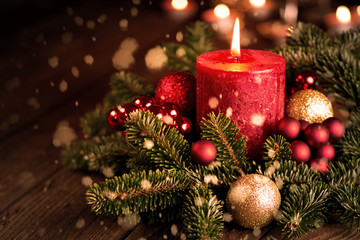Adventskerze mit Weihnachtsschmuck und Schnee