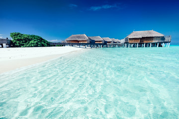 Summer hotel with houses standing in the water on Maldives