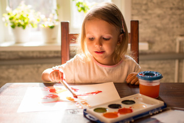 A little girl at the table and drawing with watercolors