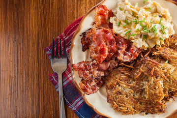 Hash browns. Potato pancakes with crispy fried bacon and scrambl