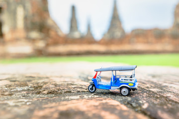 Tuk Tuk Toy Model lay on brick with blurred Wat Chaiwatthanaram Background. ,Thailand ancient buddhist temple ,Asian Travel and Vacation Concept Image ,Shallow DOF selective focus on Tuktuk steer.