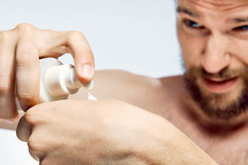 bearded man squeezes a little cream on his hand