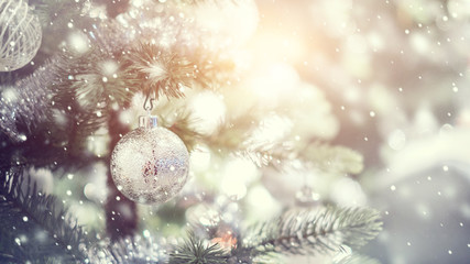 Silver and white bauble hanging from a decorated Christmas tree with bokeh and snow, copy space. Xmas holiday background.
