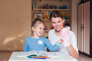 happy mother and daughter playing puppet pig and studying