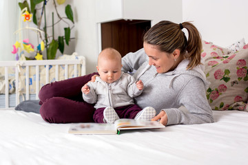Young mother, reading a book to her baby boy, showing him pictures