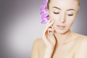 gorgeous woman face with orchid flower over grey background