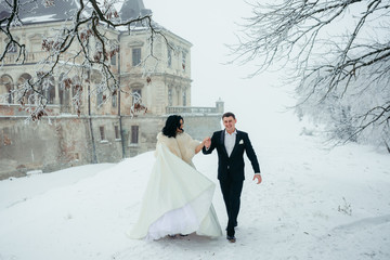 Cheerful newlyweds are holding hands and walking along the meadow near the old castle covered with snow.