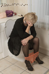 Blond woman sitting on the toilet with hands on her head