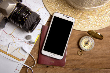 Travel planning with map, smartphone, passport, camera, compass, earphone and straw hat