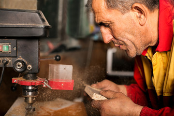 carpenter using drill press to mae hole in wooden plank