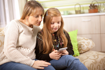 Family and technology, woman and her adult daughter using smartphone