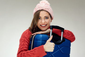 Portrait of smiling woman in red hugging with suit case and doing thumb up.