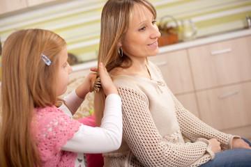 daughter combing hair of her mother in room