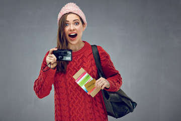Happy surprising woman holding camera, credit card with passport and tickets.