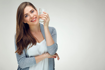 Portrait of smiling woman with long hair holding water glass.