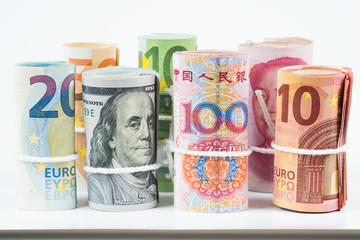 Currencies and money exchange trading concepts. The rolls of various currencies US Dollar, Euro and Chinese yuan banknotes isolated on white background.