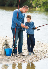 Young man and son fishing with rods
