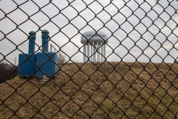 Flint Michigan Water Crisis. The Flint Michigan water tower seen through a chain link fence. Flint made national headlines when the city water supply was contaminated with lead.