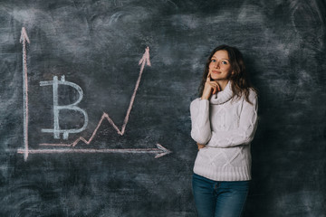 Girl watching the chart of bitcoin exchange rate drawn on black chalkboard with chalk