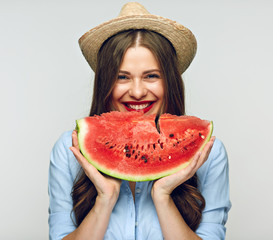 Mexican style hat wearing smiling woman eating watermelon.