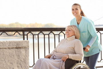 Disabled senior woman and young caregiver outdoors