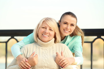 Senior woman and young caregiver outdoors