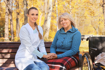 Senior woman and young nurse sitting on bench in park