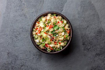 Traditional peruvian quinoa quinua salad in clay bowl, slate gray background