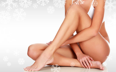 Young woman with slim body, smooth and soft skin against a grey background with snowflakes