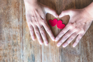 Red Heart on woman hand on wooden background with copy space. Concept for valentines day celebration or couple of love