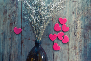 Dried flowers in a vase bottle are between a pair of hearts with a single heart on wooden background.  Valentines day concept for single people.