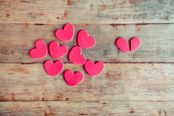 Many red hearts on left side and broken heart on the right side on wooden background. Valentines day concept for heartbroken.