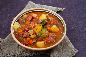 Stew, made with beef, bacon, sausages potatoes, carrots and herbs. Goulash soup bograch in a bowl. Hungarian dish