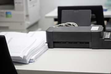 Pile of unfinished documents placed on desk with printer and copying machine.