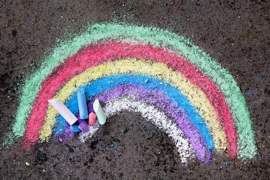 chalk drawing on asphalt: colorful rainbow