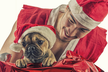 Handsome young man in Santa Claus hat and costume, with pug dog, holding colorful festive Christmas gifts to celebrate the season, on white background