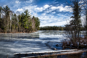 Tranquil winter lake and forest with reflection of trees and clouds on icy water
