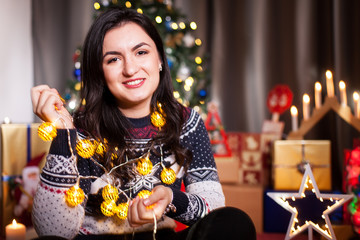 Beautiful young woman next to christmas tree and other christmas decoration