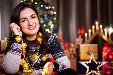 Joyful girl next to Christmas tree in decorated house