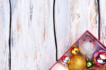 Luxury Christmas balls in box, copy space. Christmas decoration balls in box on retro wooden background, space for text, cropped image.