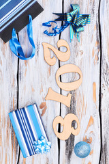 Wooden number 2018 and Christmas ornaments. Wood numbers forming the number 2018 for the new year 2018 with blue gift box, bow, Christmas ball on white rustic wooden background, top view.