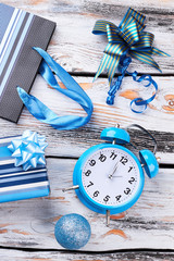 New Year ornaments and alarm clock. Blue gift box, Christmas ball, bow, shopping packet and alarm clock on old wooden background. Happy New Year.